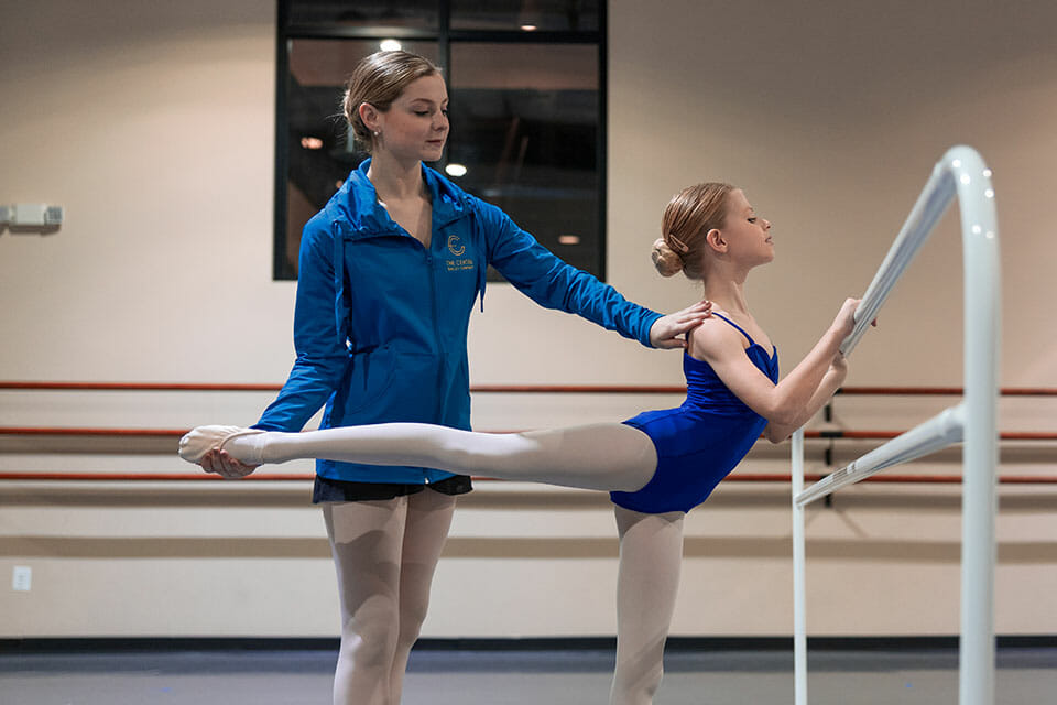 Free trial dance class ballet instruction Northern Virginia - instructor assists young student