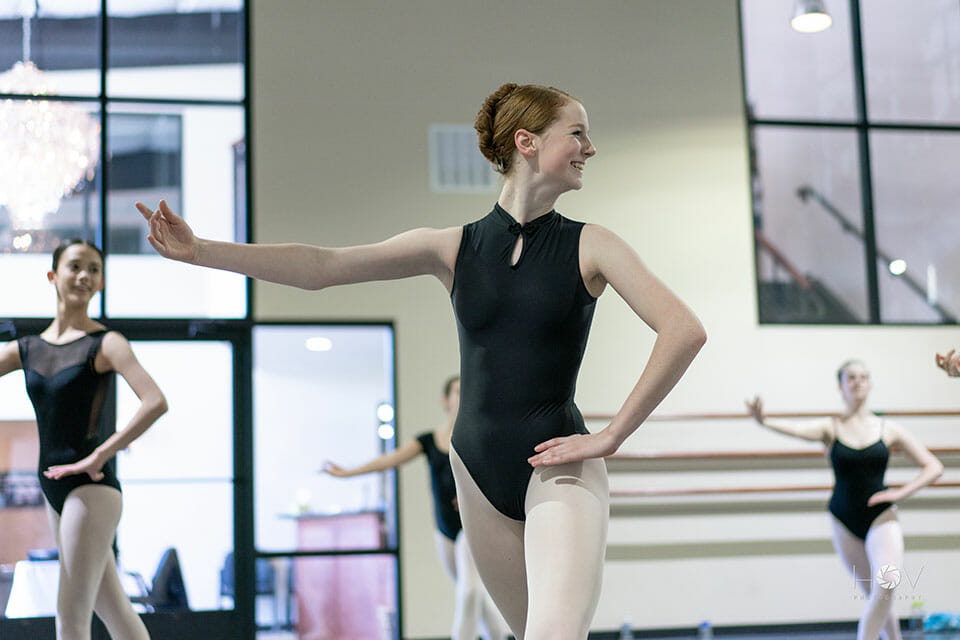 Free trial dance class ballet instruction Northern Virginia - young adult student with good form smiles for camera